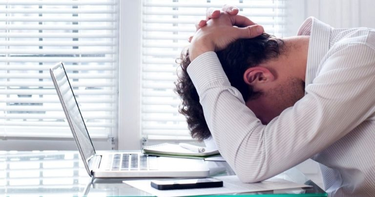 Man sat at desk with his head in his hands.