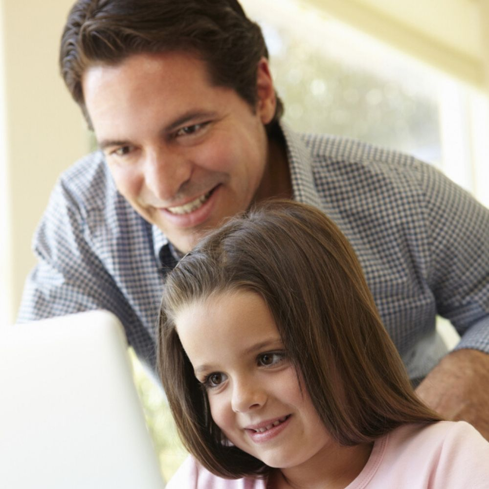 Father and daughter look at ipad learning English online together