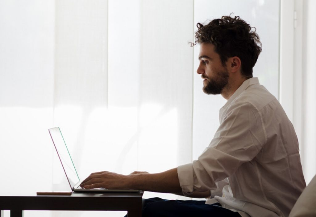 Man sits on sofa improving his career skills online