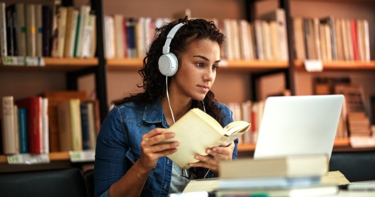 Girl with headphones studies in university library