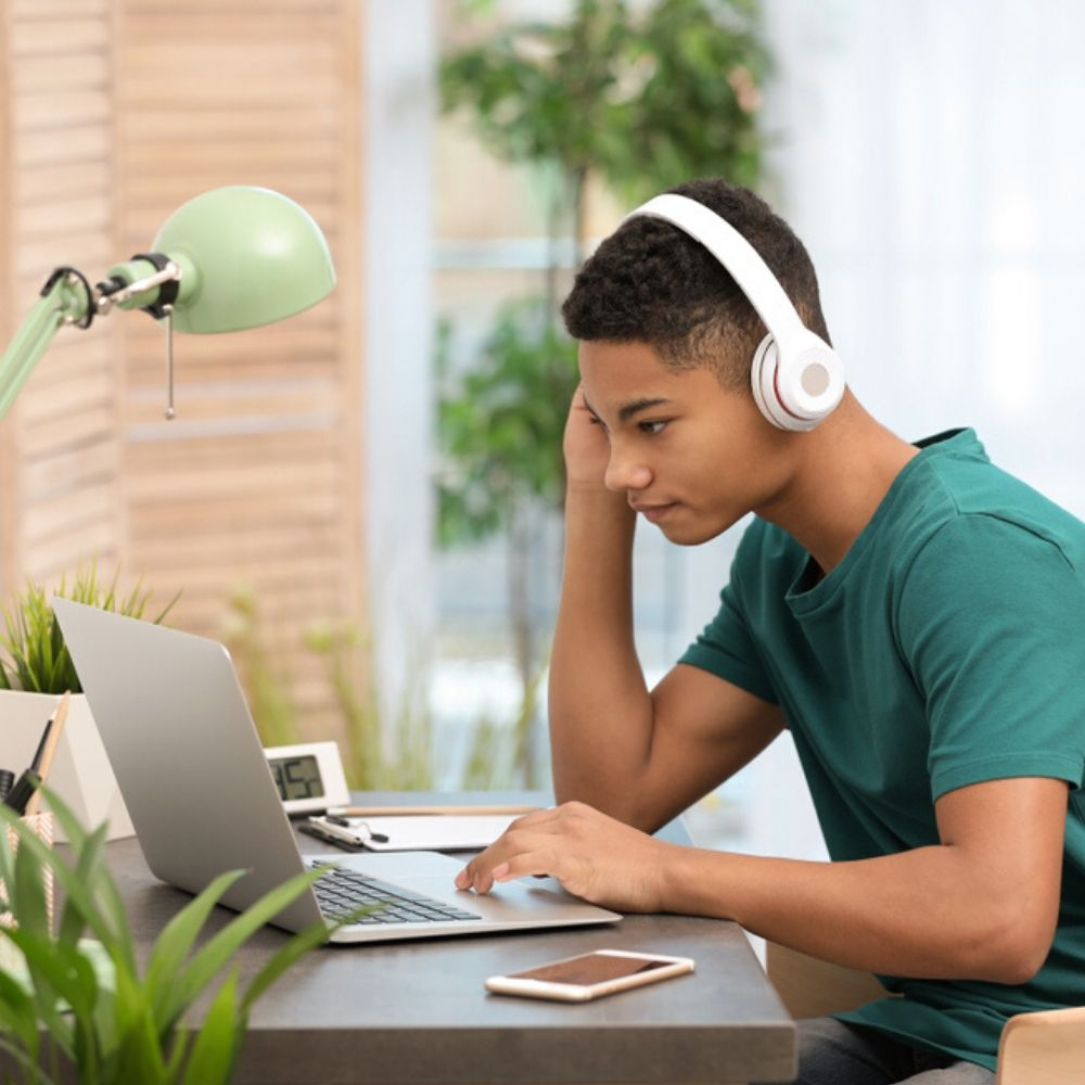 Boy with headphones learns English online