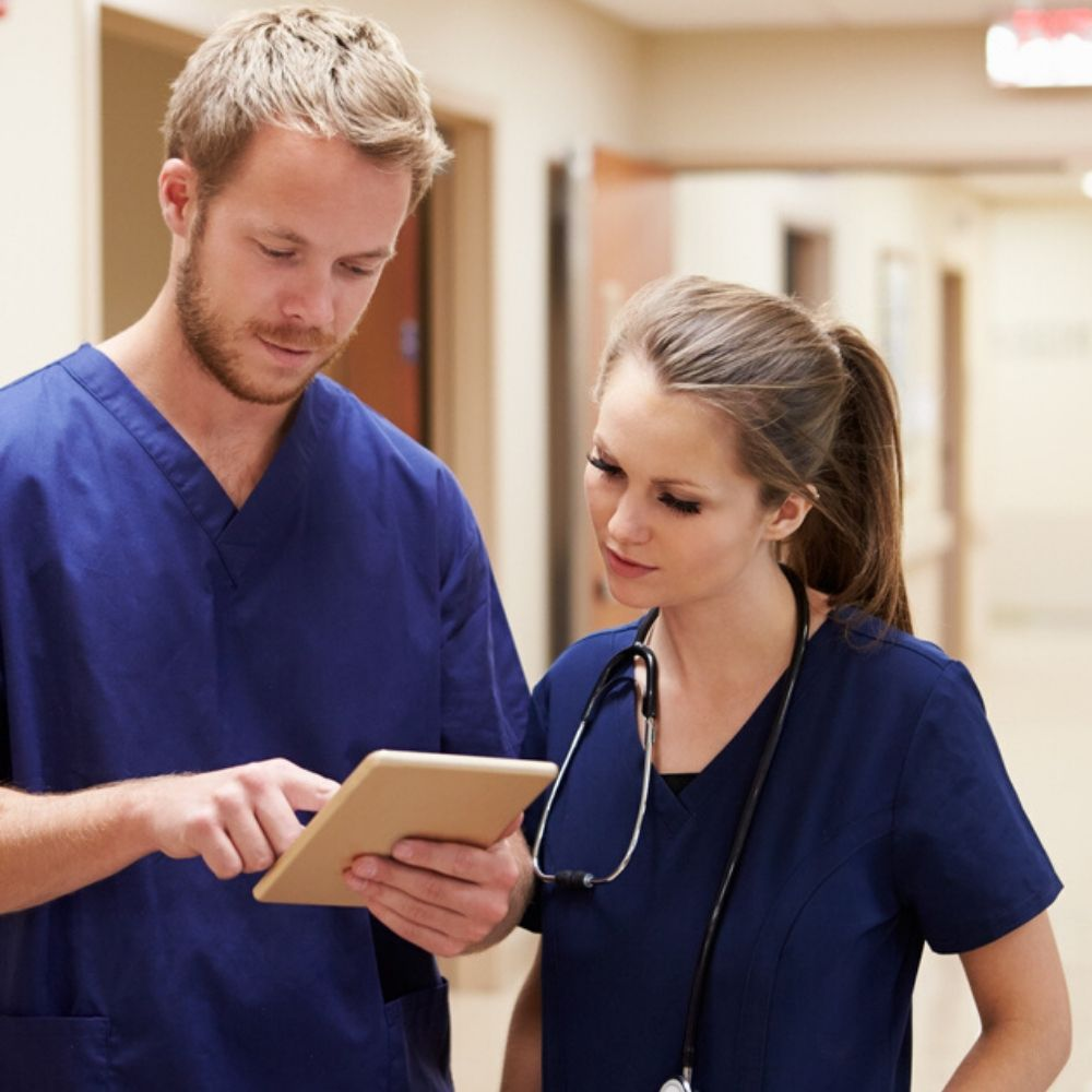 Two nurses with digital tablet in hospital