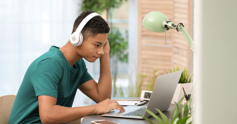 Boy in green t shirt with headphones at computer