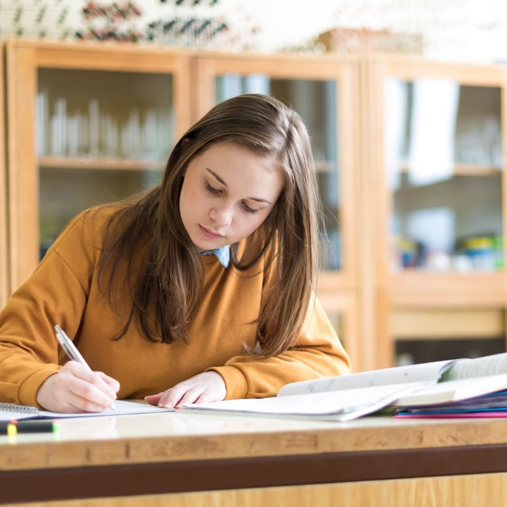 woman writing notes as she studies for cambridge exam