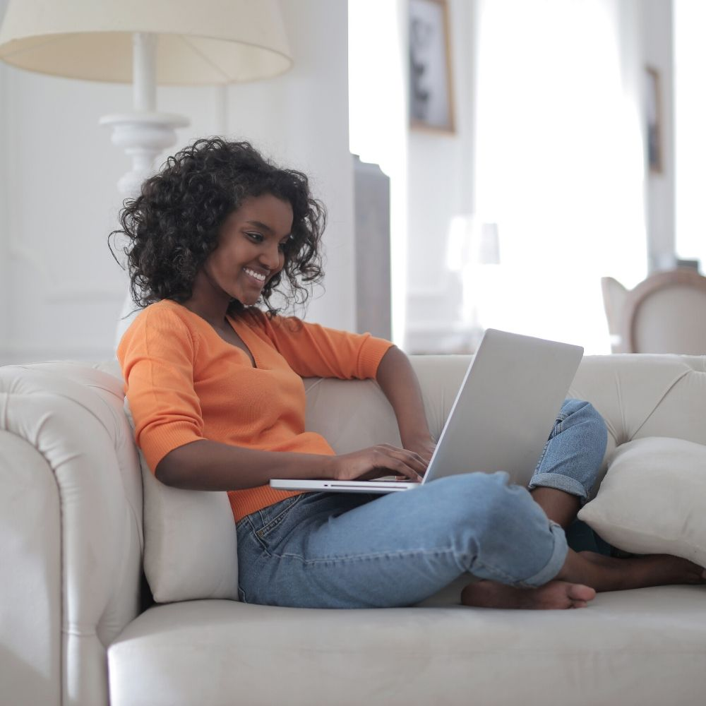 Woman on couch using laptop