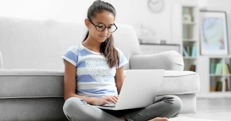 Young girl studying on laptop