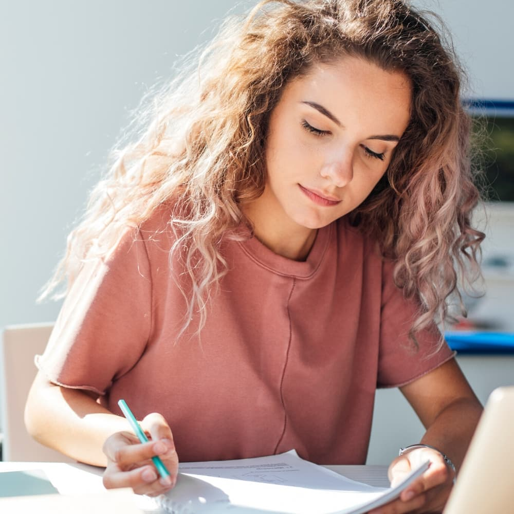 young woman wearing pink t shirt studying for test