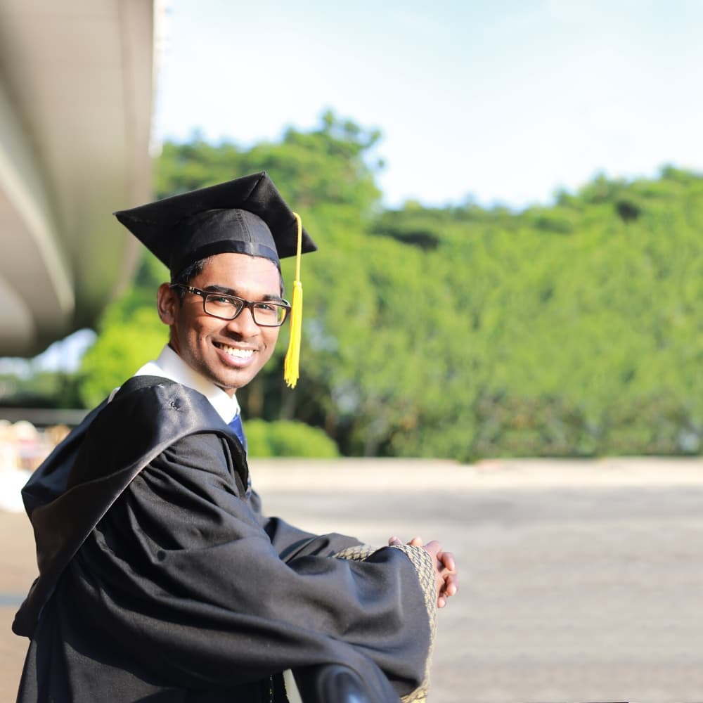 man with glasses in graduation gown and cap