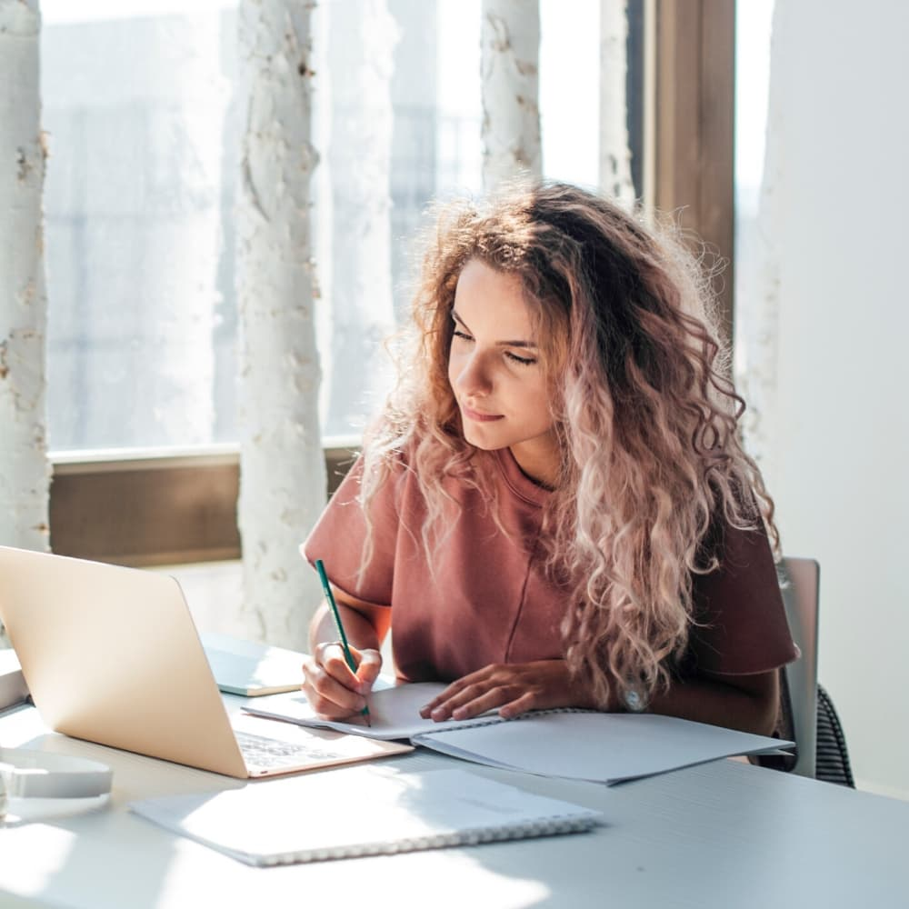 woman making notes working online