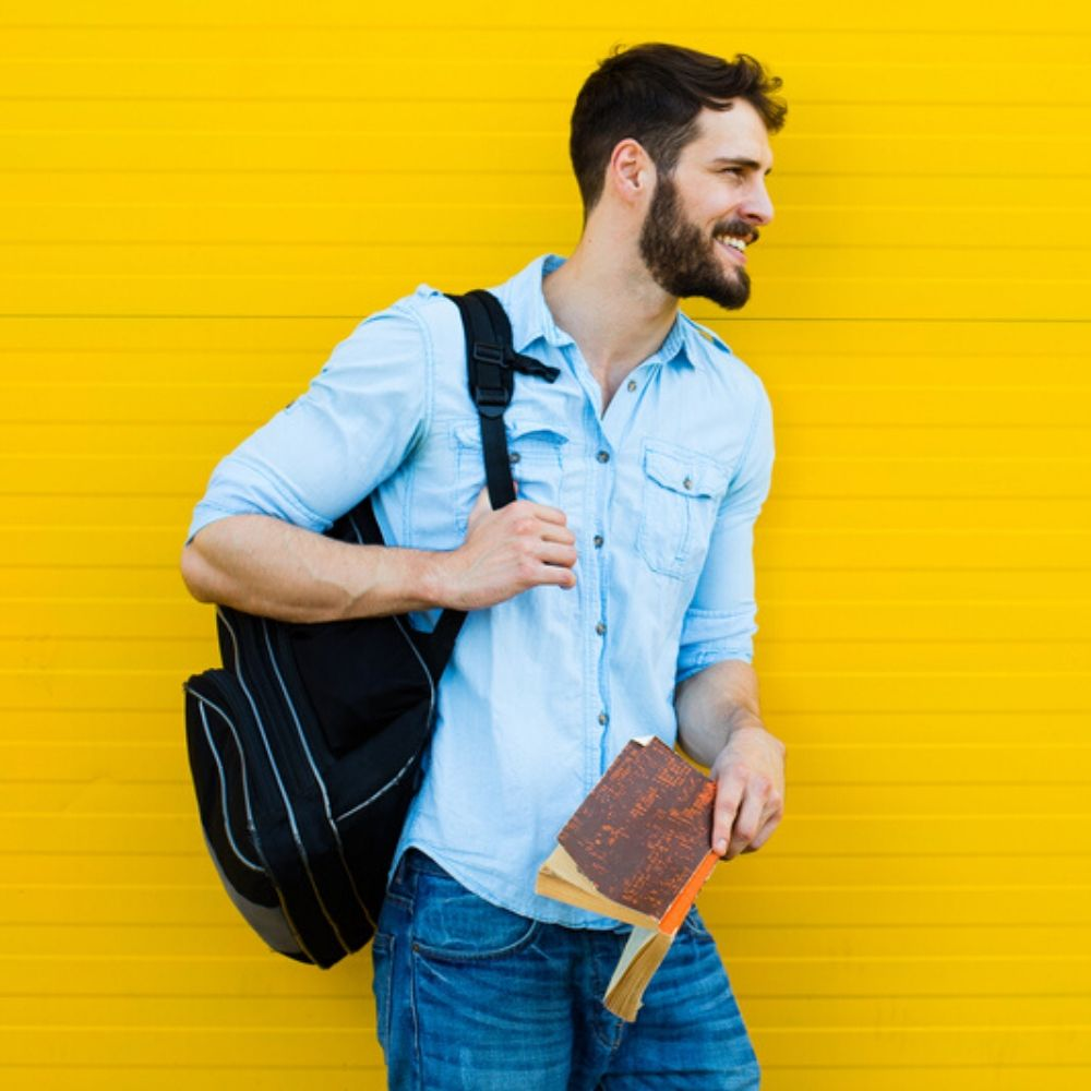 Student leaning on yellow wall smiling