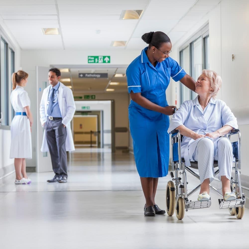 nurse speaking with patient in wheelchair