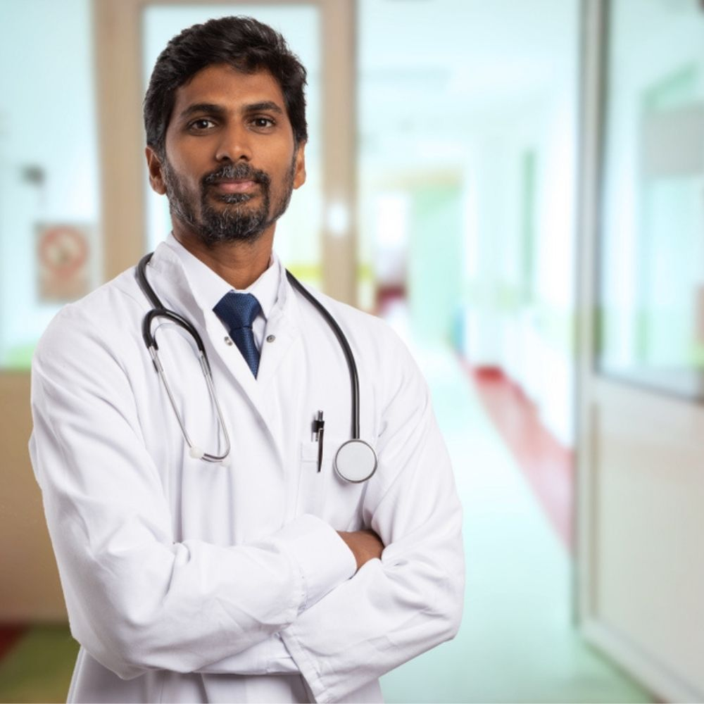 Doctor stands proudly in hospital after passing OET exam