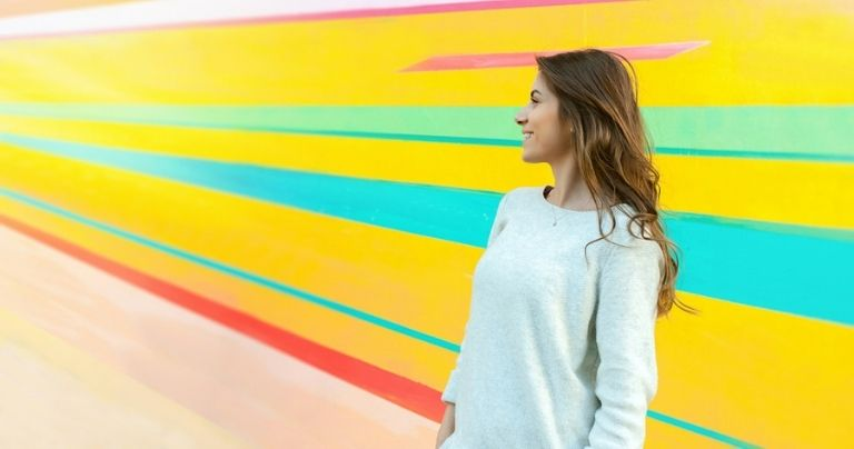 Girl in front of colourful wall