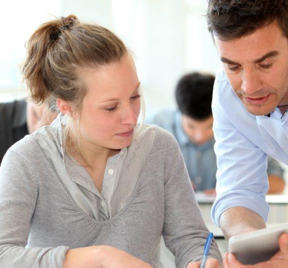 Profesor hablando con una estudiante en una clase con otros estudiantes de fondo