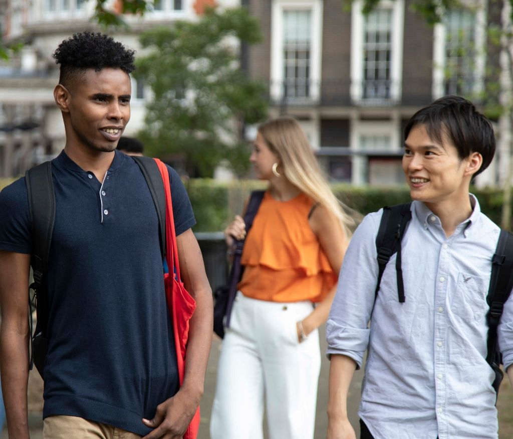 Dos estudiantes hablando y paseando por una ciudad
