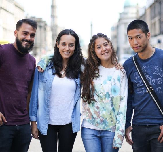 Un grupo de estudiantes jóvenes rodeándose el hombro con el brazo