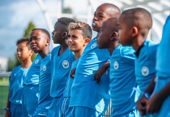 Niños formando una fila en el lateral de un campo de entrenamiento mientras escuchan las instrucciones del entrenador