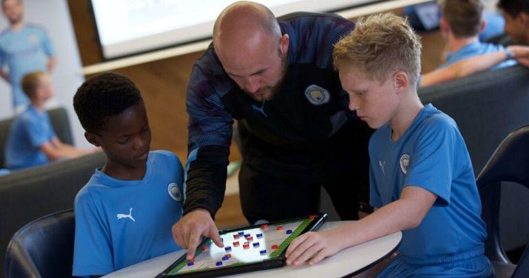 Entrenador mostrando a un equipo de jóvenes jugadores formaciones sobre una pizarra blanca en un aula