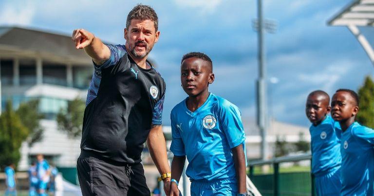 Entrenador de la Manchester City Academy hablando con un joven jugador