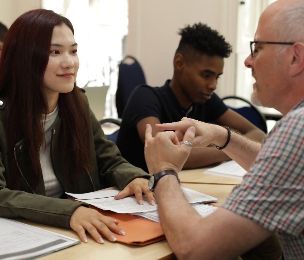 Estudiantes de curso NCUK en clase hablando con un profesor
