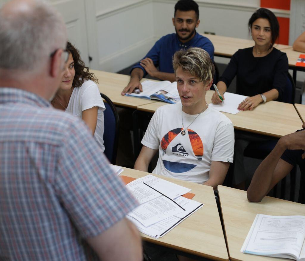 Estudiantes en una clase de Acceso a la universidad del Reino Unido escuchando al profesor que aparece en primer término