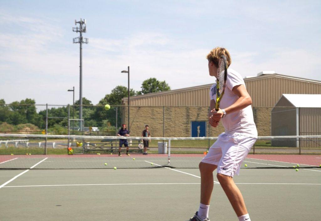 Un adolescente con ropa de tenis blanca se concentra en una pelota que pasa por encima de la red