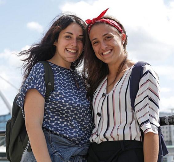 Dos estudiantes sonrientes al aire libre con la brisa agitando su pelo