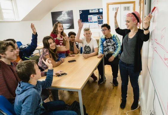 Estudiantes levantando la mano en clase en la escuela de BSC en Edimburgo