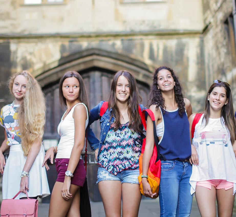 Un grupo de jóvenes estudiantes caminando junto a un edificio histórico