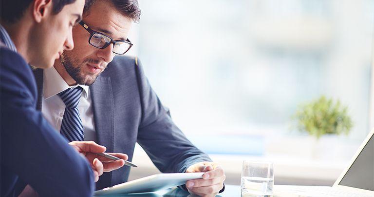 Dos hombres en traje hablan en una mesa de oficina