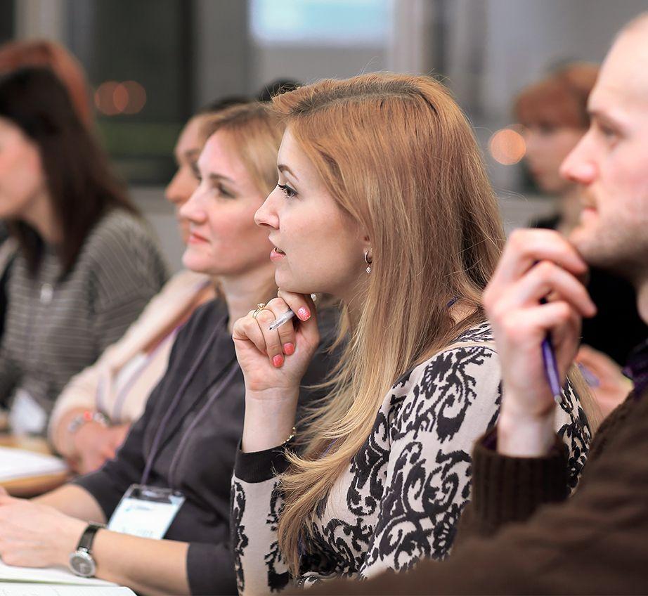 Mujer pelirroja escuchando y tomando notas en una sala llena de gente