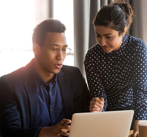 Un hombre trabajando en un portátil con una compañera de pie junto a él