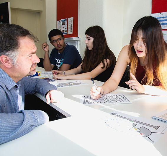 Profesor hablando con una estudiante mientras ella escribe