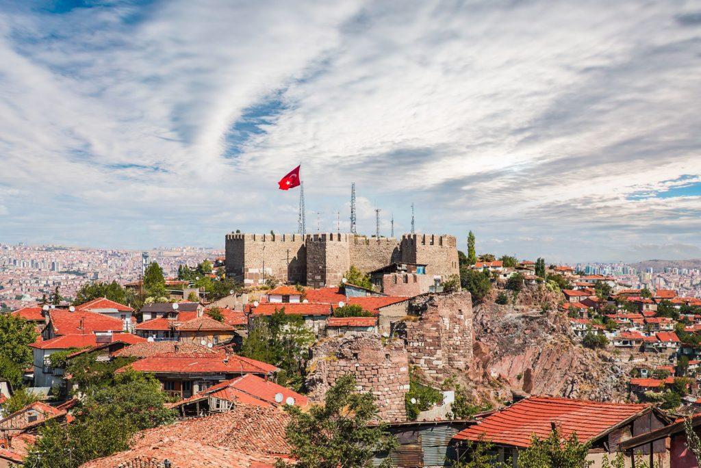 Imagen de una fortaleza en lo alto de una montaña con la bandera turca ondeando y una ciudad a sus pies