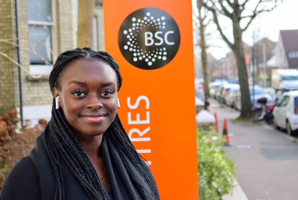 Jasmin delante del cartel de la escuela de BSC en Brighton