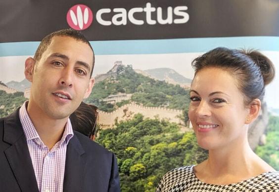 Nick Alexandrou (Director General de BSC) y Faye (Cactus Worldwide) frente al logotipo de Cactus