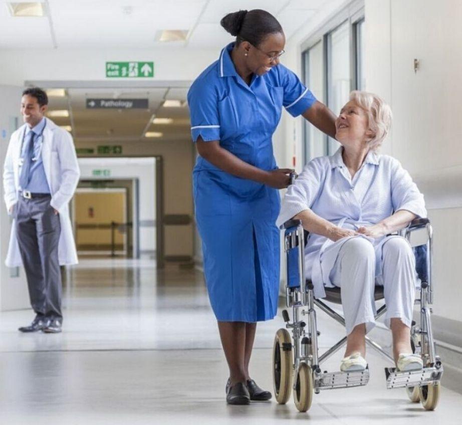 Profesionales de la salud con una paciente en un pasillo
