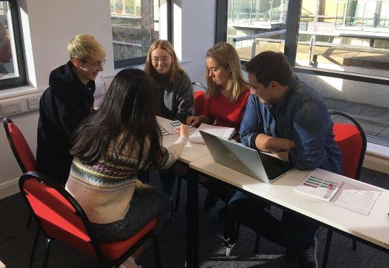 Grupo de estudiantes estudiando en un aula luminosa y soleada