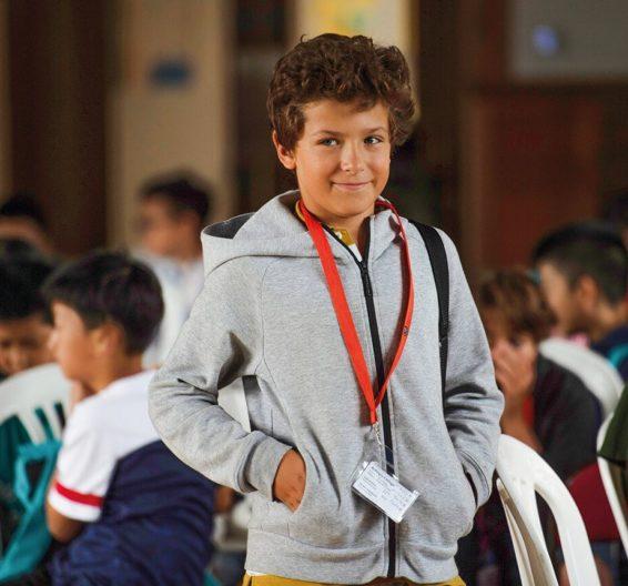 Un alumno feliz mira a la cámara en el salón de actos de la escuela