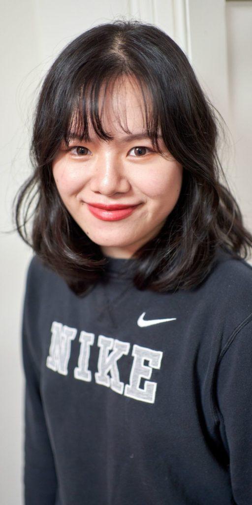 Joven asiática apoyada en una pared