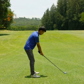 Boy practising golf on fairway