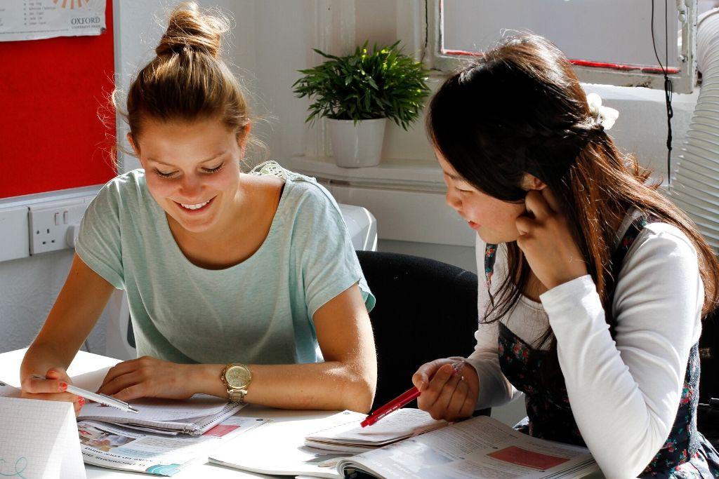 Dos alumnos estudiando en clase