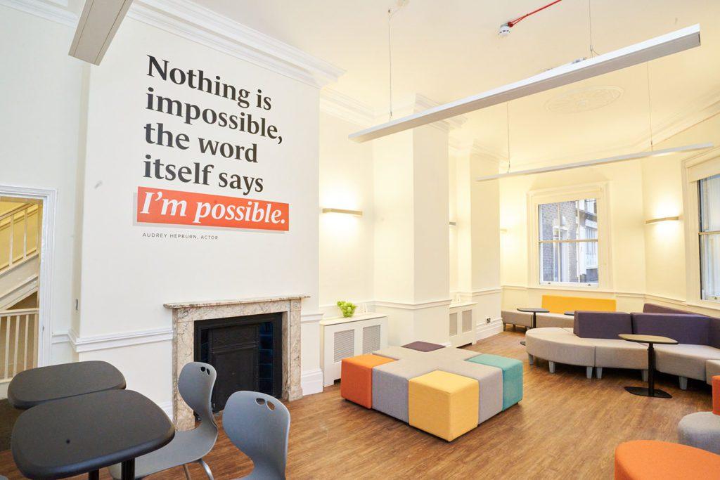 Une pièce lumineuse et colorée au BSC de Londres avec une citation inspirante sur le mur