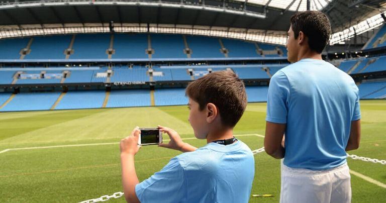 Des garçons prennent des photos du stade d'Etihad lors d'une visite guidée