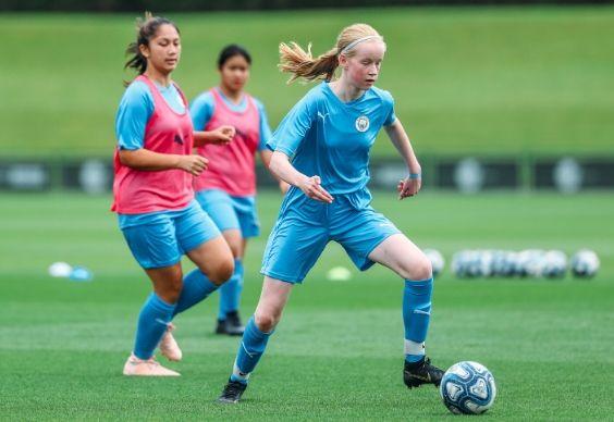Filles portant la tenue de Manchester City jouant au football sur un terrain extérieur