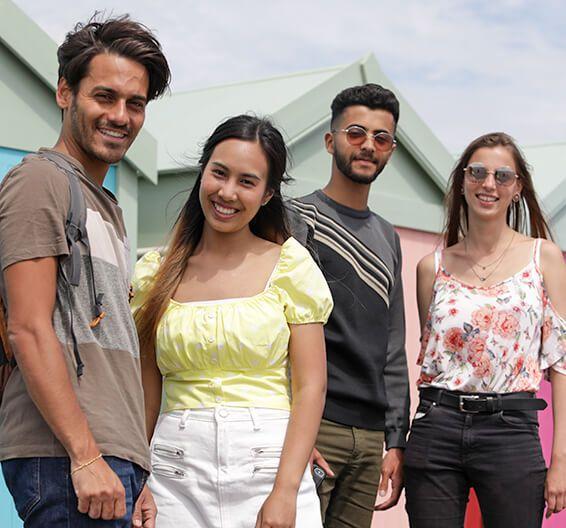 Des étudiants sourient devant des cabanes de plage colorées