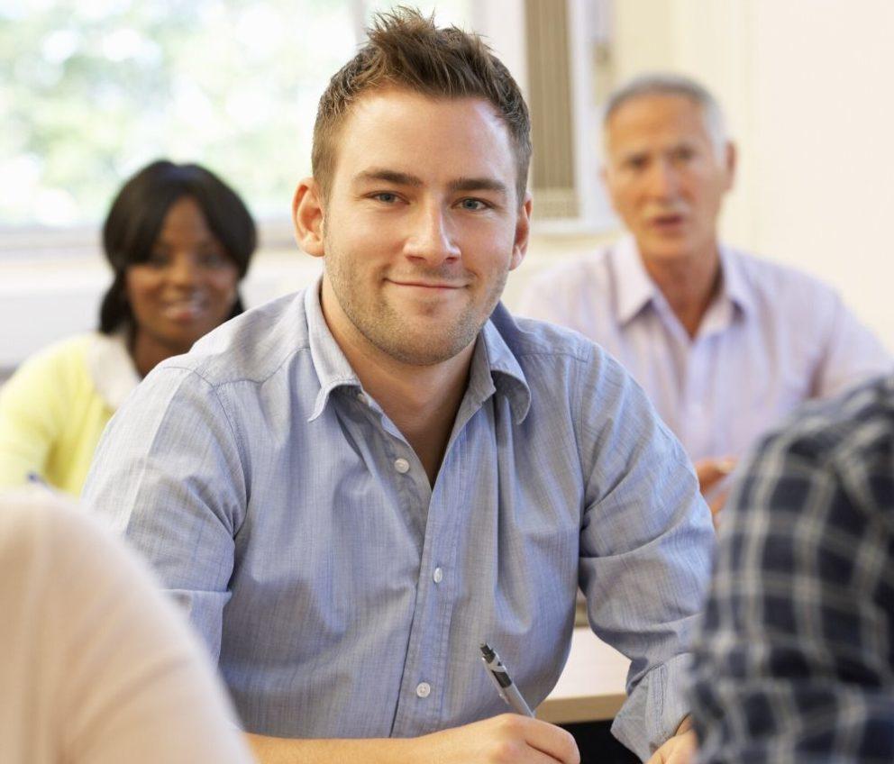 Un étudiant souriant à la caméra avec d'autres étudiants en arrière-plan