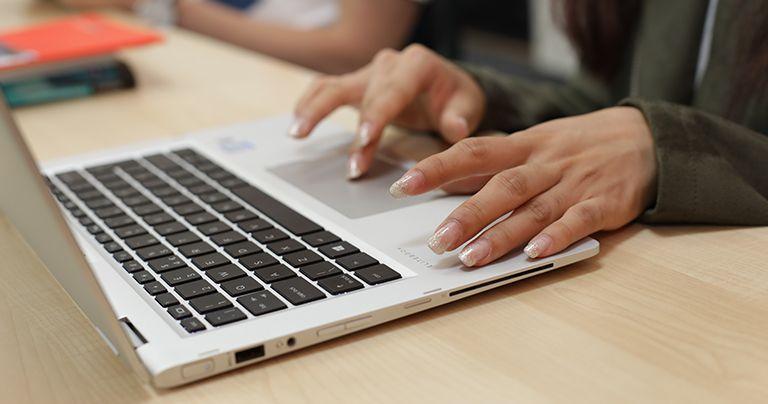 Gros plan de mains tapant sur un ordinateur portable