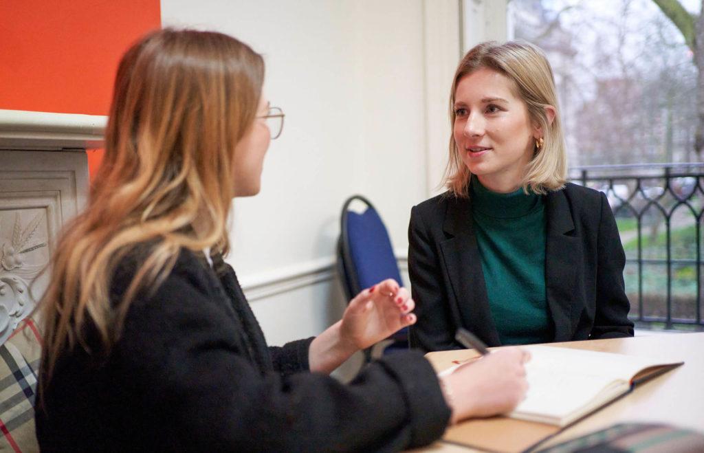 Deux jeunes femmes blondes discutant en prenant des notes