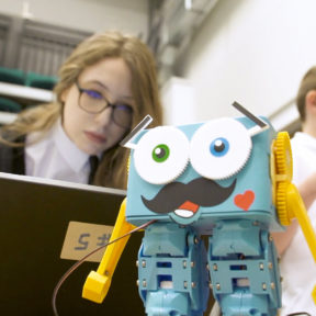 A girl looks up from her laptop to watch a robot, on the Coding and Robotics course